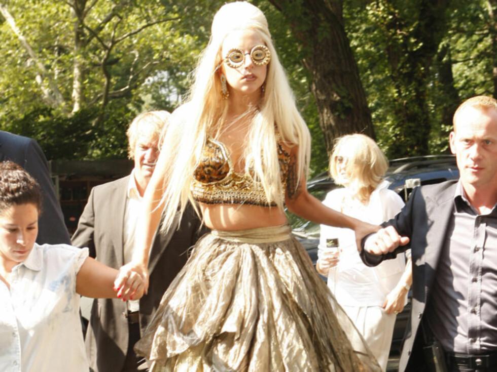 MENNESKE-KRYKKER: Popikonet Lady Gaga lot seg støtte av to assistenter på vei til  photo-shooten i New York mandag. Foto: All Over Press