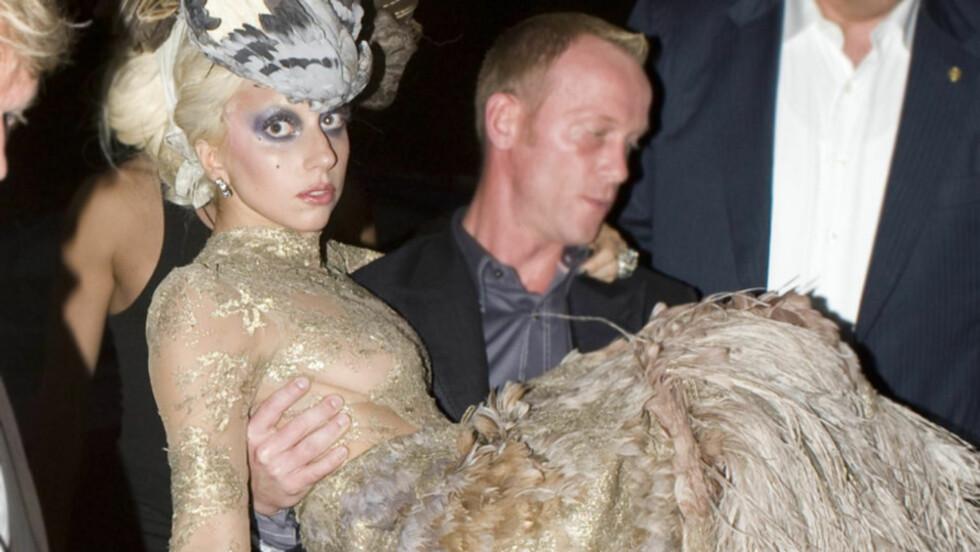 SLITEN: Lady Gagas utstuderte antrekk og ekstremt upraktiske sko, gjorde at hun måtte støttes og bæres til og fra location da hun deltok i en foto-shoot med Annie Leibovitz mandag. Her ankommer hun The Meatpacking District i New York for dagens siste f Foto: All Over Press