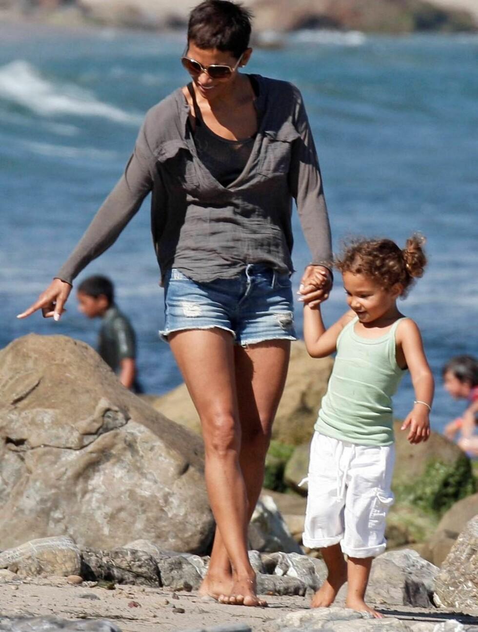 <strong>FLO OG FJÆRE:</strong> Hally Berry lærer datteren sin litt om de forskjellige tingene man kan se på en strand.  Foto: All Over Press