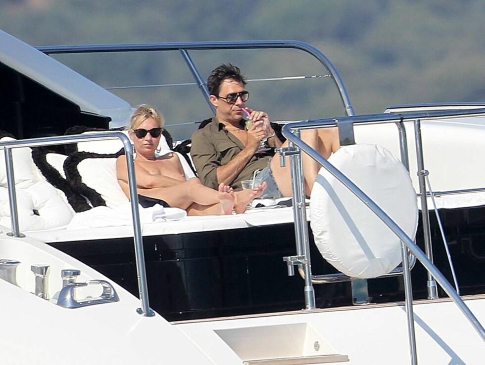KASTET KLÆRNE: Kate Moss valgte å kaste bikinitoppen under den varme Middelhavssola, mens hennes nybakte ektemann Jamie Hince kjølte seg ned med litt kald drikke. Foto: All Over Press