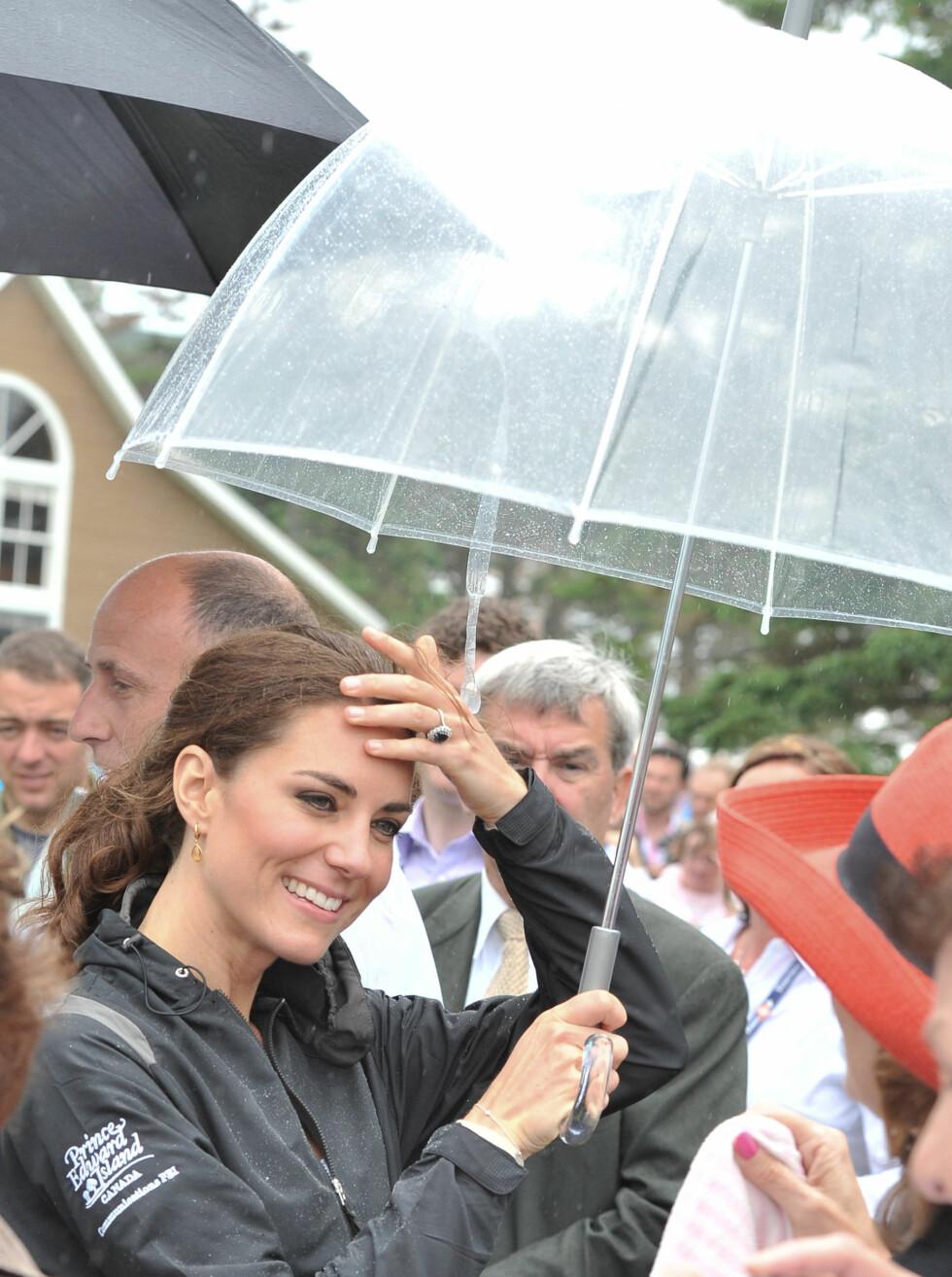 VÅT I HÅRET: Prinsesse Kate måtte fram med paraplyen.  Foto: All Over Press