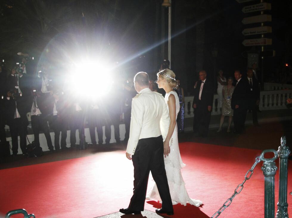 BLITZLYS: Fyrst Albert og prinsesse Charlene på vei inn til gallamiddag i  Monaco lørdag med fotografene fyrer løs.  Foto: Scanpix
