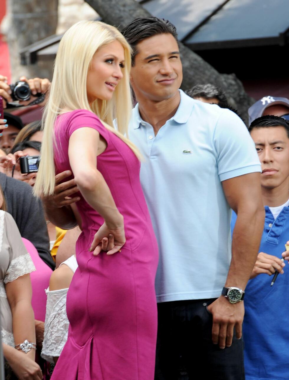 <strong>MAGEKUL:</strong> Paris Hilton vekker oppsikt i denne kjolen på grunn av kulen på magen. her med Mario Lopez. Foto: All Over Press