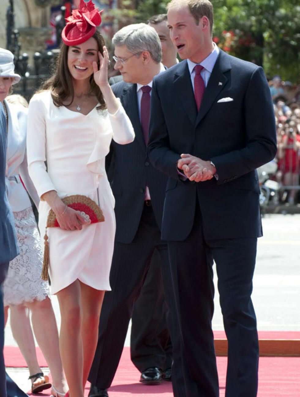 GJENBRUK: I Ottowa iførte hertuginne Kate seg kjole fra det britiske merket Reiss, som hun også brukte på de offiesielle forlovelsesbildene, stilig vifteformet veske fra Anya Hindmarch, røde pumps, en brosje lånt av dronningen - og en liten rød hatt Foto: All Over Press