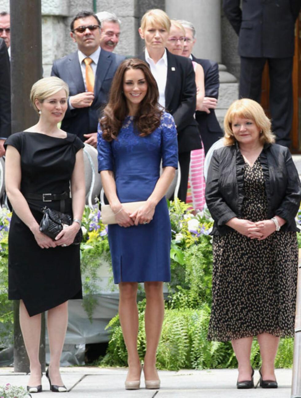 SMAKFULL:Ved siden av sine lønneblad-inspirerte assesoarer, gav hertuginne Kate (midten) et nikk til kanadisk stil gjennom denne elegante kjolen designet av Erdem Moralioglu - som er født i Montreal, men som nå bor i London.  Foto: All Over Press