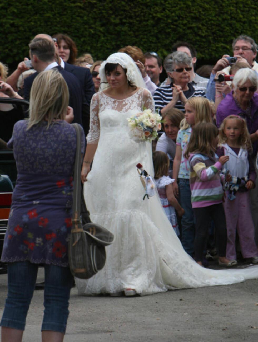 KUL MED KUL: Brud Lily Allen lot seg villig fotografere av oppmøtte landsbybeboere - mens den voksende magen var synlig i den 20-tallsinspirerte brudekjolen, som også hadde likhetstrekk med KAte Middletons brudekjole.  Foto: Stella  Pictures