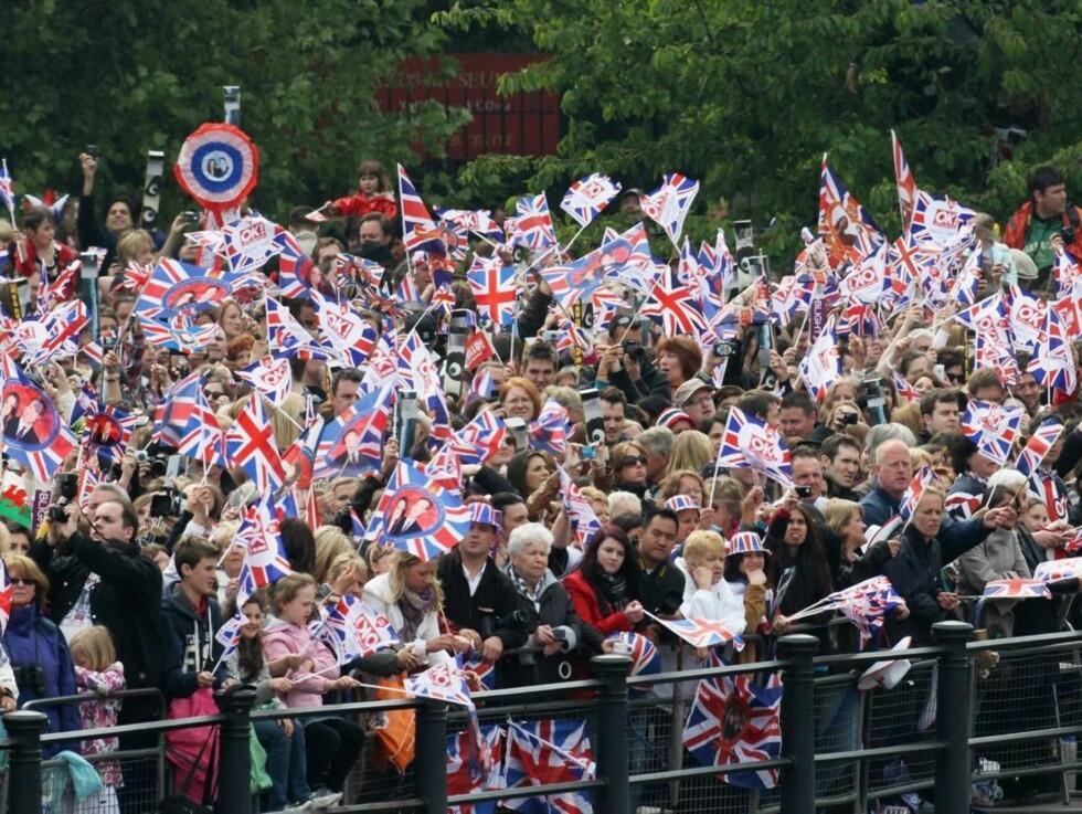 <strong>FOLKEFEST:</strong> Tusenvis av mennesker hadde samlet seg utenfor Buckingham Palace i håp om å få et glimt av det kongelige ekteparet. Foto: All Over