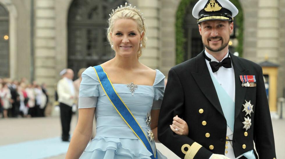 <strong>PÅ SYVENDE PLASS:</strong> Det er denne isblå kjolen som har sikret kronprinsesse Mette-Marit en plass på magasinet Time sin liste over verst bryllupskledde kongelige. Her avbildet sammen med kronprins Haakon under bryllupet til Sveriges kronprinsesse Victoria  Foto: All Over Press