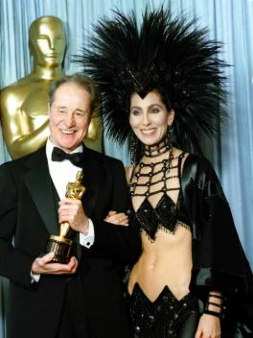 ** FILE ** Cher wears a creation by designer Bob Mackie as she poses with actor Don Ameche after presenting him with the Oscar for best supporting actor at the Academy Awards in Los Angeles, March 24, 1986. Over the years, Cher has been a prime and often Foto: AP