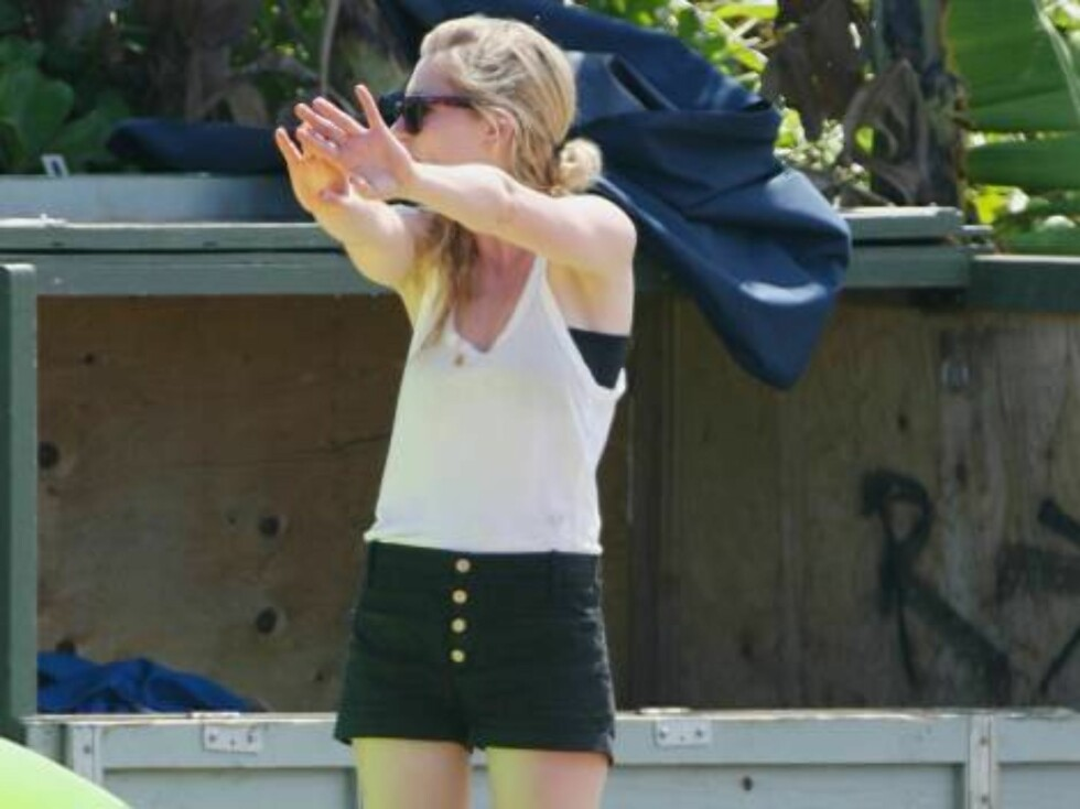Kirsten Dunst was on the beach in Maui against with her friends, enjoying the sun and singing while applying suntan lotion and giving the photographers the shaka with young twin men. She was wearing a bikini and left the beach in black shorts and a white Foto: All Over Press