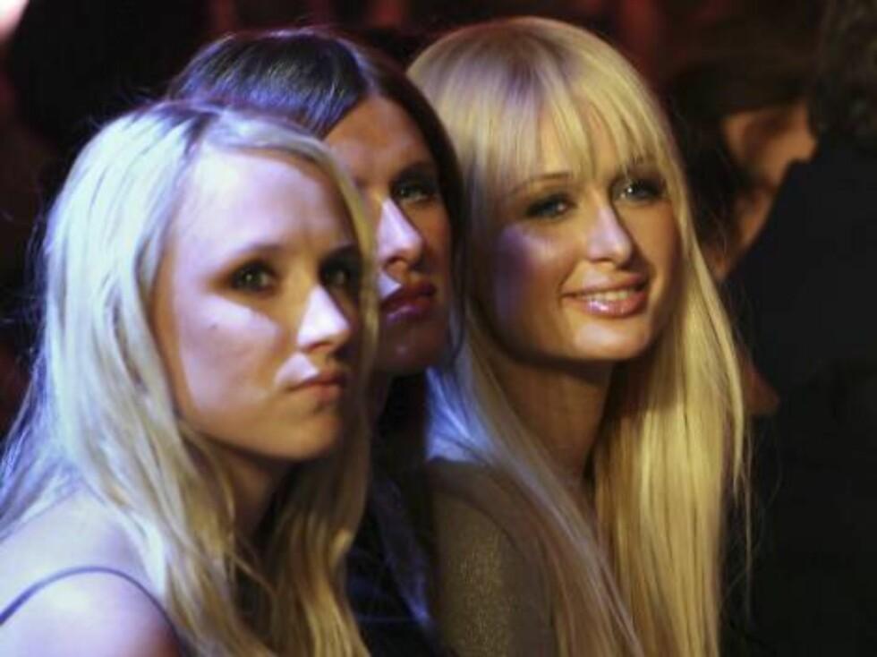 Paris og den ny-single søsteren Nicky følger med på catwalken. Foto: AP/Scanpix
