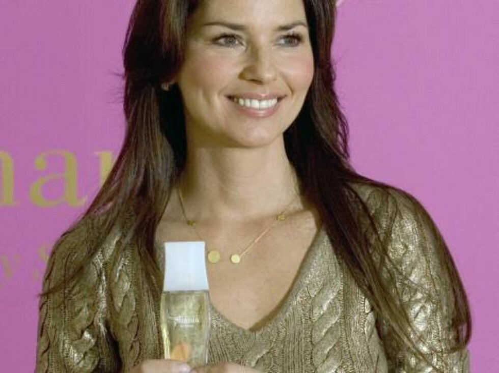 """Singer Shania Twain poses for photographers with her new perfume, """"Shania,"""" between interviews in Toronto, Thursday Nov. 17, 2005. Shania was in Toronto on Thursday to promote her new fragrance. (AP Photo/CP,Adrian Wyld) Foto: AP/Scanpix"""