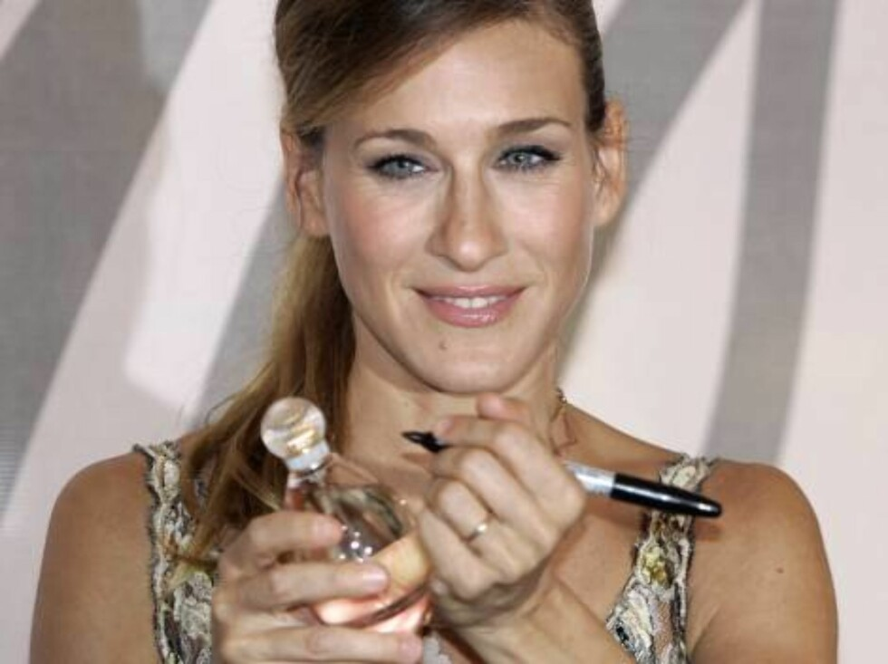 """Actress Sarah Jessica Parker signs a bottle of her new perfume """"Lovely"""" at the Lord & Taylor department store in New York City, Friday, Sept. 9, 2005. The former star of the cable television """"Sex and the City"""" series also greeted customers.  (AP Photo/Jef Foto: AP/Scanpix"""