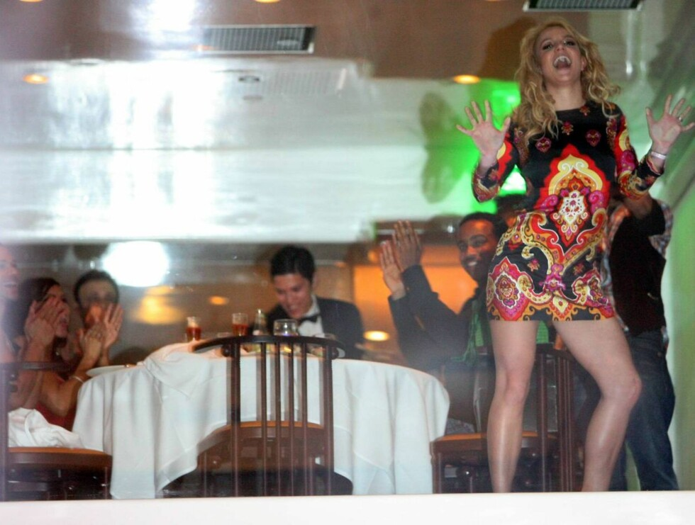 GLAD: Britney stilte i en svært kort-kort kjole på bursdagen sin. Her underholder hun både gjestene og paparazziene. Foto: All Over Press