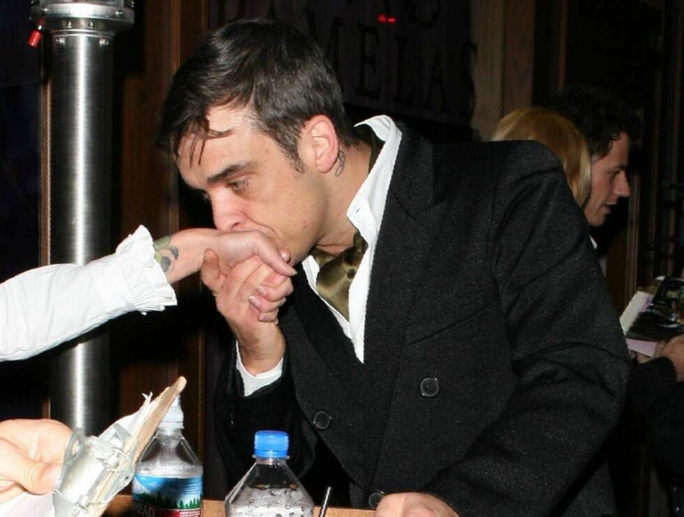 FLØRT: Robbie gir en heldig frøken et lite kyss på lanken. Men det var alt han fikk gi henne denne kvelden ... Foto: All Over Press
