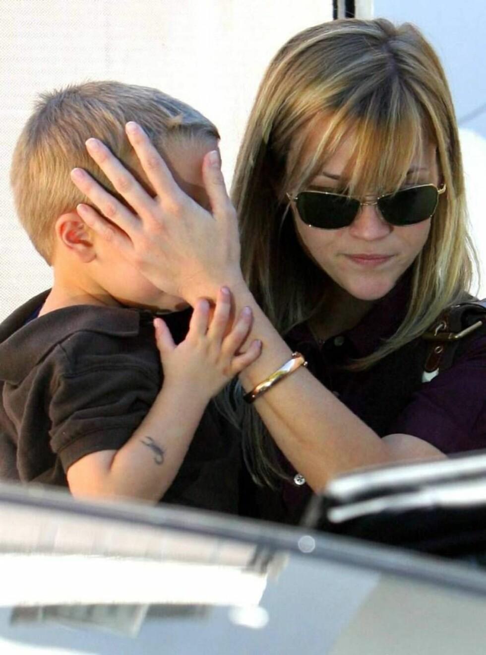 BESKYTTENDE MOR: Reese prøver å skjerme sønnen Deacon fra fotografene. Foto: All Over Press