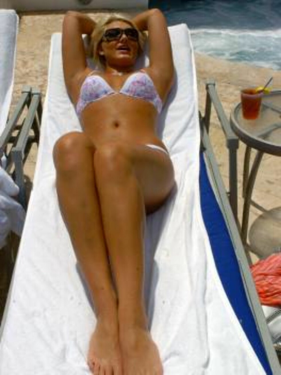 MIAMI 2006-05-01  A very blonde and very tan Brooke Hogan, daughter of the one and only Hulk Hogan, works the camera while relaxing poolside in Miami this May. The young woman is showing off her new body, just in time for the release of her debut cd. Foto: STELLA PICTURES