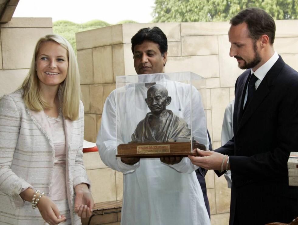 LA KRANS: Kronprinsparet la på krans på Mahatma Gandhis grav i New Dehli.  Her mottar Mette-Marit og Haakon en Gandhi-skulptur. Foto: SCANPIX