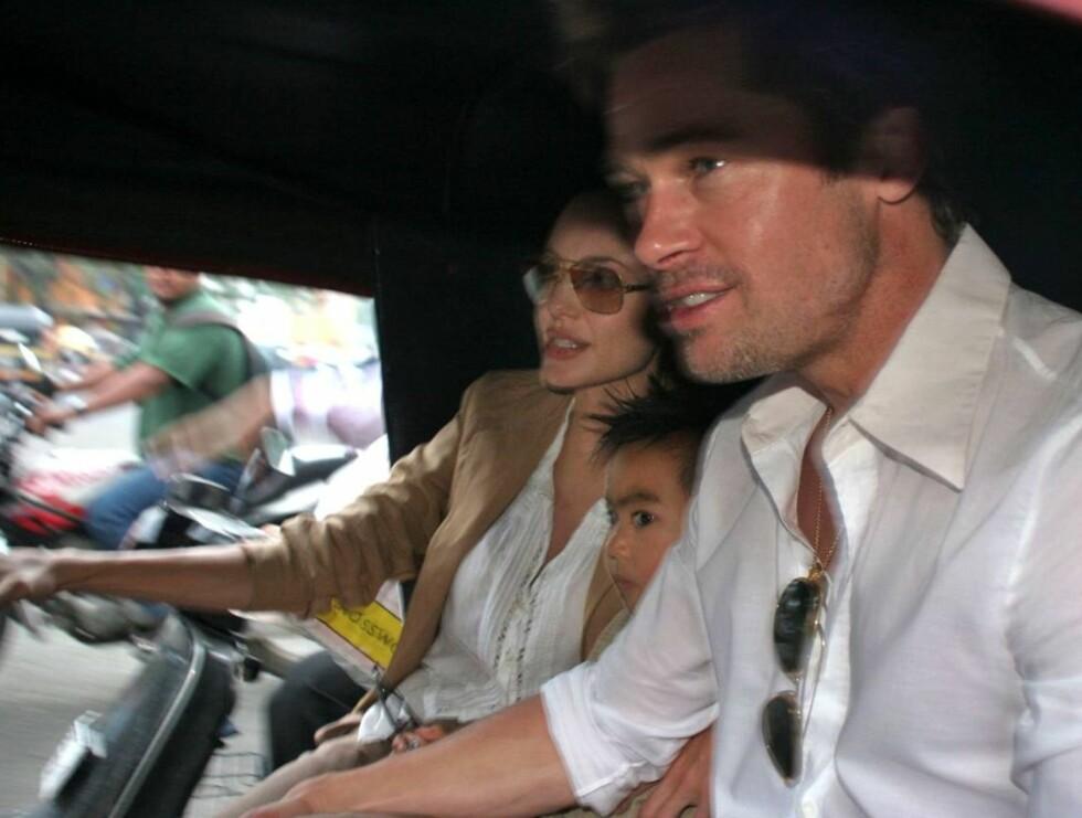 Angelina Jolie, sønnen Maddox og Brad Pitt på vei fra hotellet hvor en fotograf ble angrepet av parets livvakt. Foto: AP