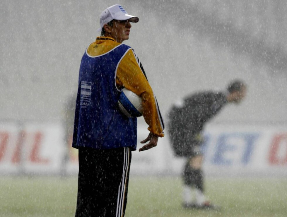 A boy stands in the heavy rain during a Greek Super League soccer match between AEK Athens and Iraklis at the Olympic stadium of Athens, on Monday, Sept. 18, 2006. (AP Photo/Thanassis Stavrakis) Foto: AP/Scanpix