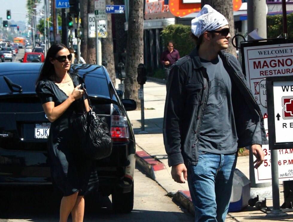 HOLDT SEG BAK: Demi holdt seg bak Ashton på veien til restauranten. Skammet hun seg over klesdrakten hans? Foto: STELLA PICTURES