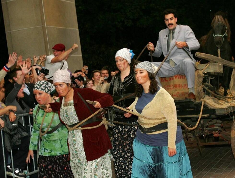 MANNSSJÅVINIST: Borat på filmfestivalen i Toronto - med kvinnene foran og hesten oppå vognen. Foto: All Over Press