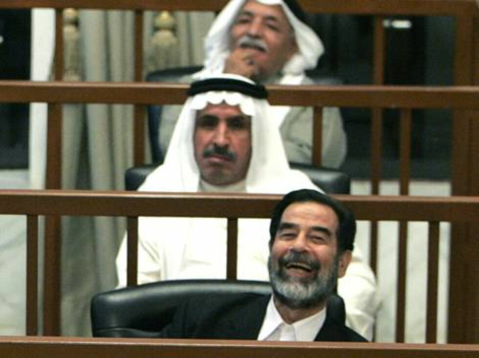 Former Iraqi president Saddam Hussein laughs while listening to defence witness testimony during his trial in the fortified Green Zone in Baghdad, Iraq, Tuesday May 30, 2006. Seated behind Saddam are Mizhar Abdullah al-Ruwayyid, 2nd row, and Taha Yassin R Foto: AP/Scanpix
