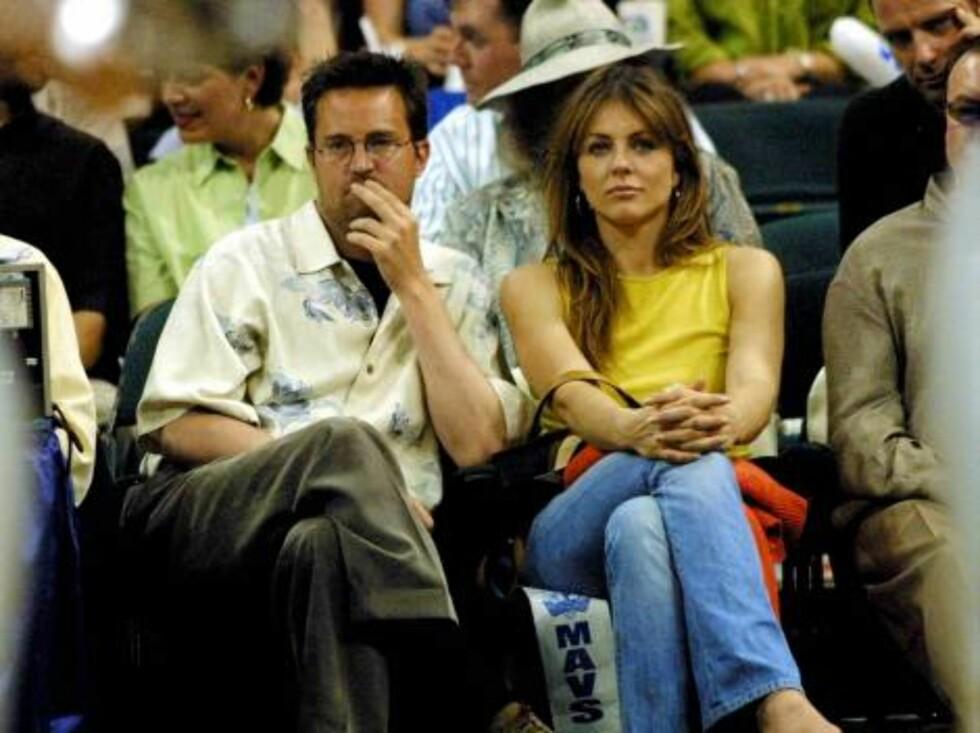 Skuespilleren Matthew Perry og den sexy modellen Elizabeth Hurley ser på basketball. Foto: All Over Press