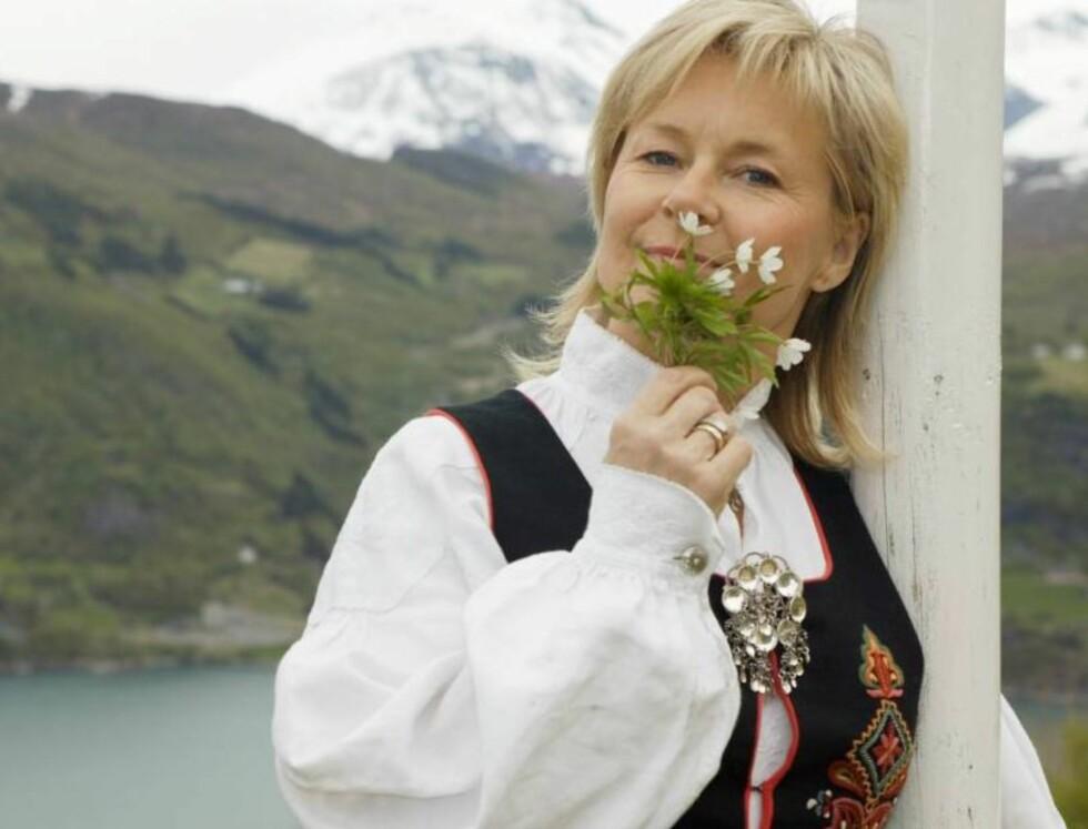DOFTER PÅ BLOMMORNA: Elisabeth Andreassen i det nasjonalromantiske hjørnet, der hun lukter på markblomster og har Storfjorden og fjellet Varden i bakgrunnen. Foto: Thomas Lillehagen Røyert/Se og
