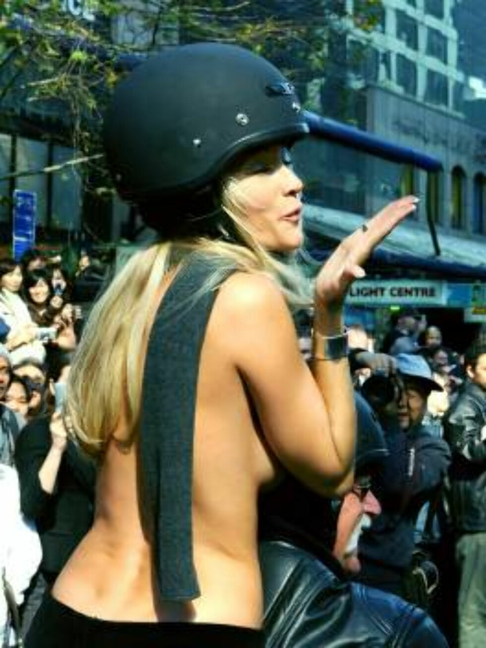 """One of twenty-five topless pornstars blows a kiss as she rides on a motorcycle down Auckland, New Zealand's Queen Street Wednesday, Aug. 23, 2006. Dubbed the """"Boobs on Bikes"""" parade, it is being used to publicize an erotica show which opens in Auckland la Foto: AP"""