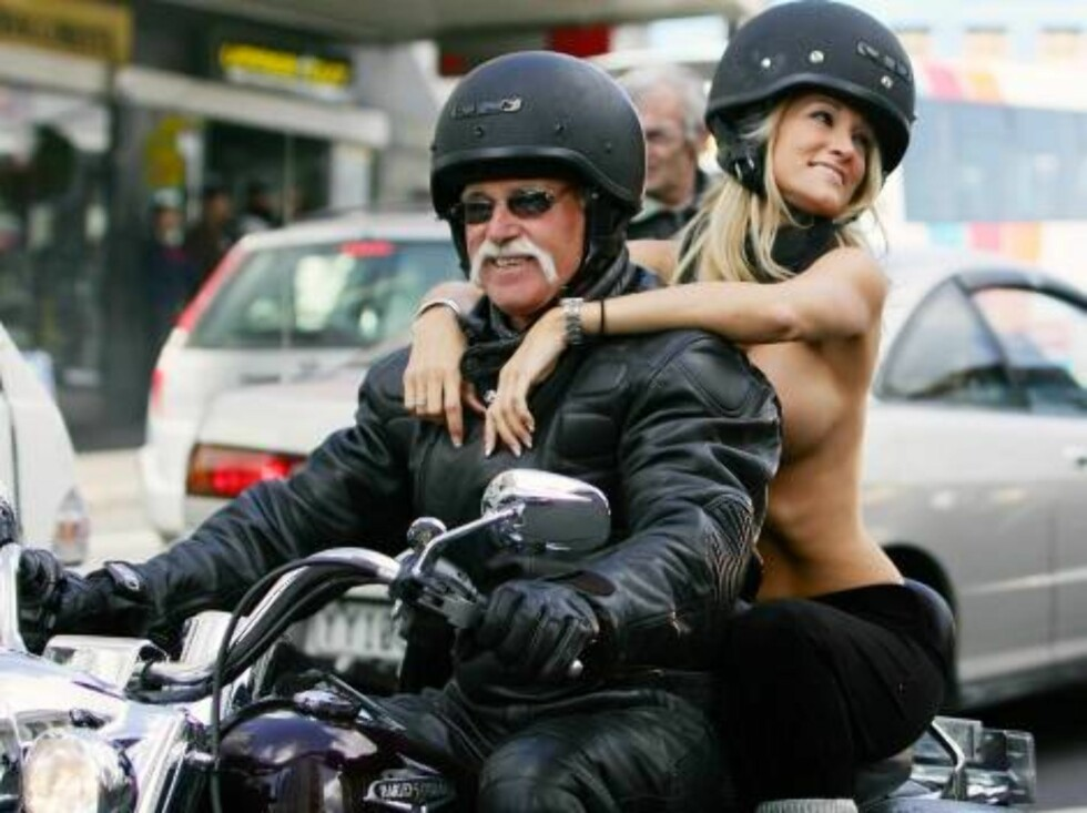 """One of twenty-five topless pornstars rides on a motorcycle down Auckland, New Zealand's Queen Street Wednesday, Aug. 23, 2006. Dubbed the """"Boobs on Bikes"""" parade, it is being used to publicize an erotica show which opens in Auckland later this week. (AP P Foto: AP"""