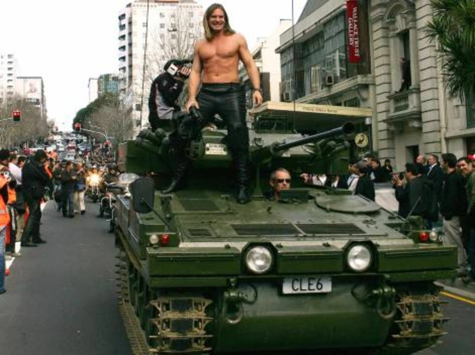 """A male pornstar, one of twenty-five, rides on an armored vehicle down Auckland, New Zealand's Queen Street Wednesday, Aug. 23, 2006. Dubbed the """"Boobs on Bikes"""" parade, it is being used to publicize an erotica show which opens in Auckland later this week. Foto: AP"""