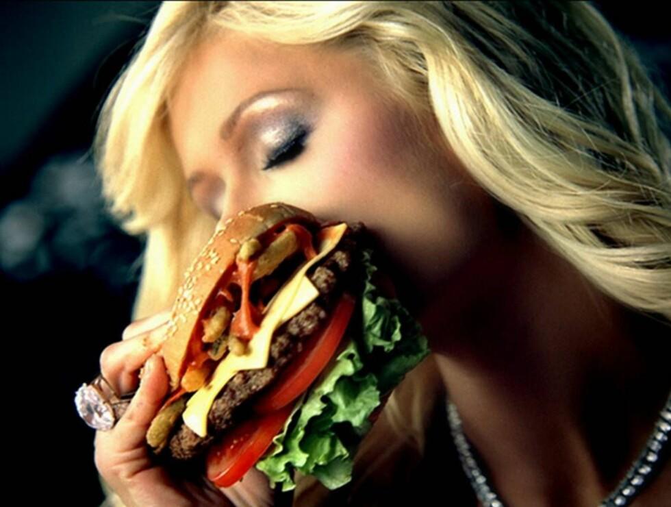 GLAD I MAT: Paris Hilton har stilt opp i reklamekampanjer for hamburgere og ser ut til å sette pris på en kjapp matbit.