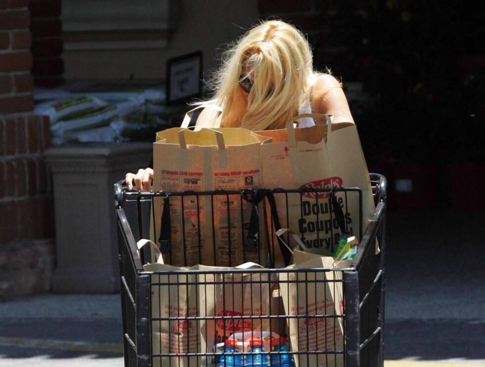 TITTEI: Pamela Anderson gjemmer seg bak handlevogna. Foto: All Over Press