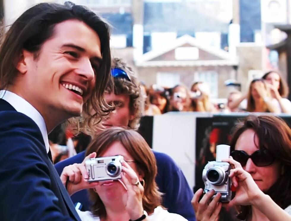 GLAD: Orlando Bloom hilser på fans under premieren i London. Foto: AP