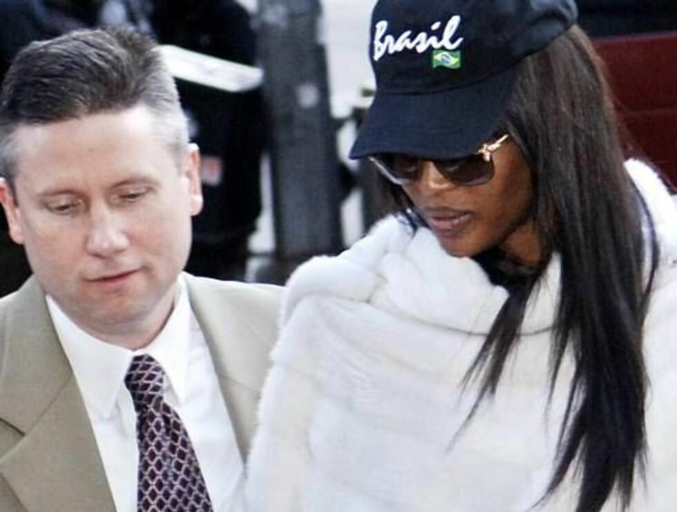 FOR RETTEN: Naomi føres inn i retten av politimenn i sivil. Foto: AP/Scanpix