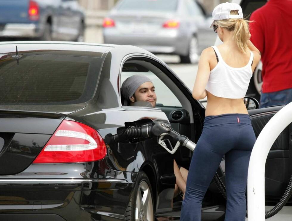 FULL TANK: Mena fyller bensin, mens kjæresten kikker på. Og utsikten er jo fin... Foto: All Over Press