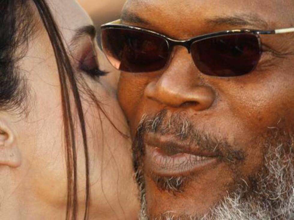 """Italian actress Monica Bellucci, left, kisses American actor Samuel L. Jackson as they arrive for the screening of the film """"Marie-Antoinette,"""" at the 59th International film festival in Cannes, southern France, on Wednesday, May 24, 2006.  (AP Photo/Laur Foto: Scanpix AP"""