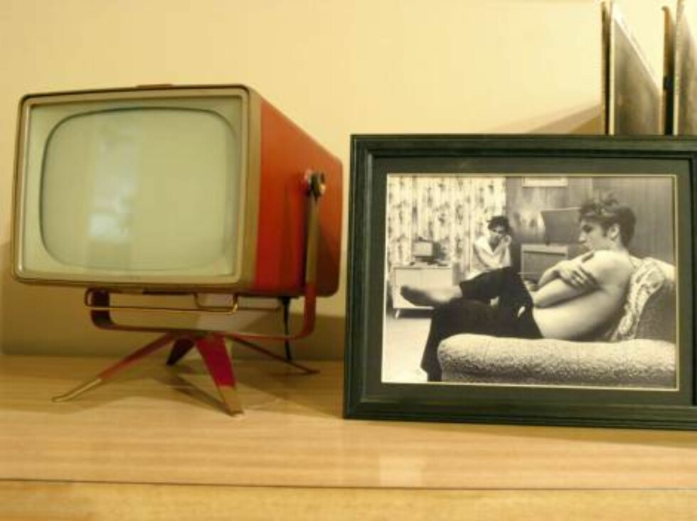 """MEMPHIS, TN - APRIL 12:  A vintage television stands next to a picture of Elvis Presley in his former home at 1034 Audubon Drive April 12, 2006 in Memphis, Tennessee. The home, purchased by the King of Rock 'n Roll in 1956 with earnings from his hit """"Hear Foto: All Over Press"""