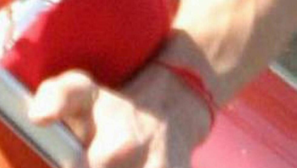 RØD KLUT: Båndet som viser at Ashton bekjenner seg til den omstridte sekten.  Foto: All Over Press