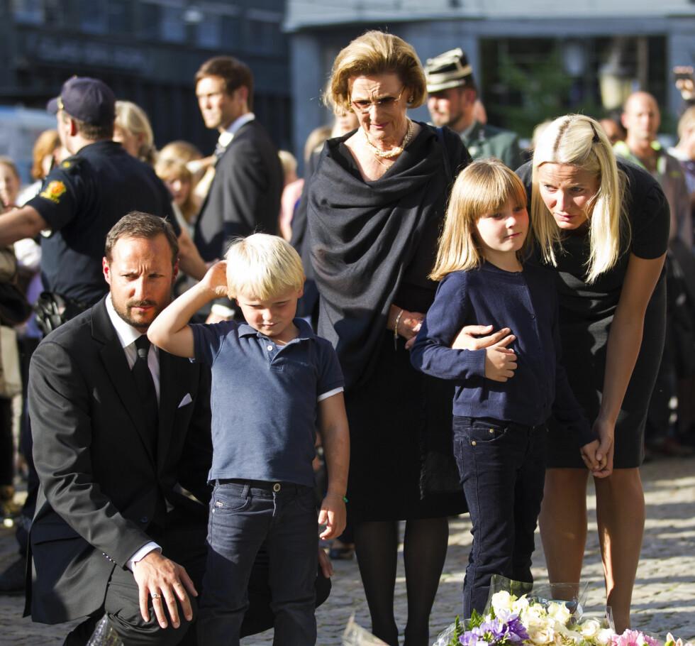 TO TIÅR SENERE: I 2011 hadde kongeparet vært på tronen i 20 år, og vi fikk erfare at deres rolle ble viktigere enn noen gang tidligere. Hele kongefamilien tok aktivt del i sorgarbeidet etter terroren som rammet oss 22. juli. Her ser dronning Sonja og svigerdatter Mette-Marit, sønnen kronprins Haakon og barnebarna prins Sverre Magnus og prinsesse Ingrid Alexandra på blomsterhavet utenfor Oslo Domkirke. FOTO: NTB Scanpix