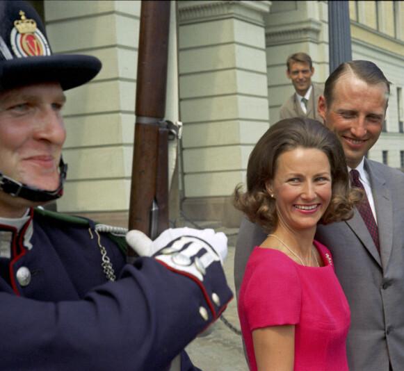 GOD STEMNING: Kronprins Harald og Sonja Haraldsen fotografert på slottsplassen etter forlovelsen i 1968. Her fotografert sammen med garden utenfor Slottet på slottsplassen, og det er tydelig at også de satte pris på at den flotte kronprinsen endelig fikk lov til å gjøre Sonja til sin kone. Foto: NTB