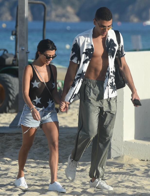 HOLDT HENDER: Kourtney og kjæresten Younes gikk tur på stranden i solnedgangen. Foto: NTB Scanpix