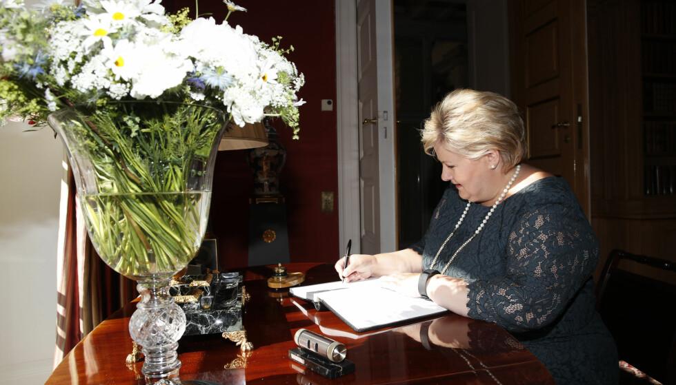 SIGNERER: Statsminister Erna Solberg signerer gratulasjonsprotokollen på Slottet i anledning av dronning Sonjas 80-årsdag. Foto: Terje Bendiksby / NTB scanpix