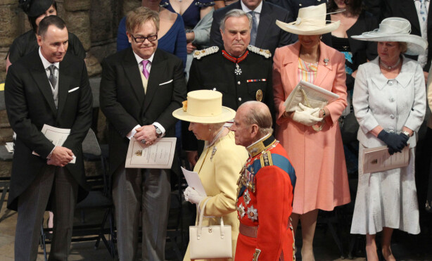 I PRINSEBRYLLUP: David Furnish og Elton John (bak t.v.) følger med mens dronning Elizabeth og prins Philip finner plassene sine i Westminster Abbey under prinsebryllupet i april 2011. Foto: AP/ NTB scanpix
