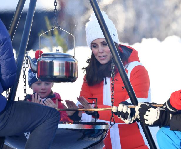 FÅR VARMEN: Hertuginne Kate benyttet anledningen til å varme hendene over bålpanna mens kronprins Haakon grillet pinnebrød. Foto: NTB Scanpix