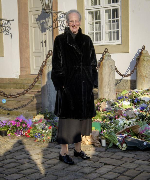 <strong>BLOMSTERHAV:</strong> Dronning Margrethe tok seg god tid til å se på kondolansebukettene, men virket ikke preget. Foto: Martin Høien / Billedbladet
