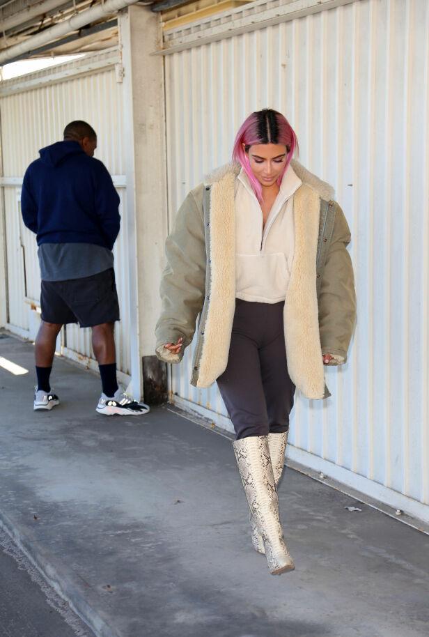 UOPPDAGET: Kanye stilte seg like gjerne langs veggen for å late vannet, selv om det ikke var lang vei igjen til varehuset. Her kan det virke som om Kim ikke har oppdaget ektemannens påfunn ennå. Foto: Splash News, NTB scanpix