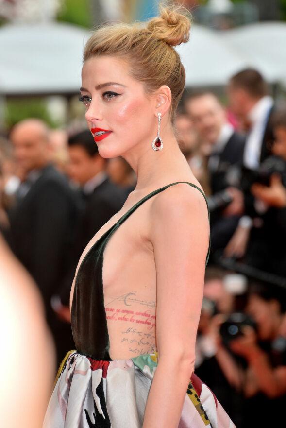 SYNLIGE TATOVERINGER: Flere av Amber Heards fargerike tatoveringer var synlige som følge av kjolens avslørende overdel. Foto: FeatureflashSHM/REX/Shutterstock/ NTB scanpix
