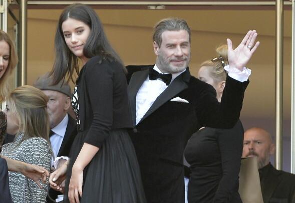 I GODT HUMØR: John Travolta vinket til fotografene bak ryggen på datteren Ella på vei inn til filmvisningen. Foto: Timm/face to face/REX/Shutterstock/ NTB scanpix